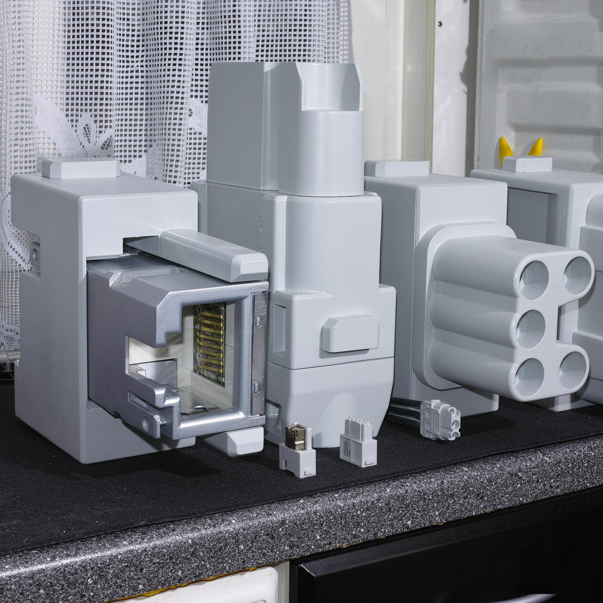 Steckermodelle vergrößert (Originale im Vordergrund)